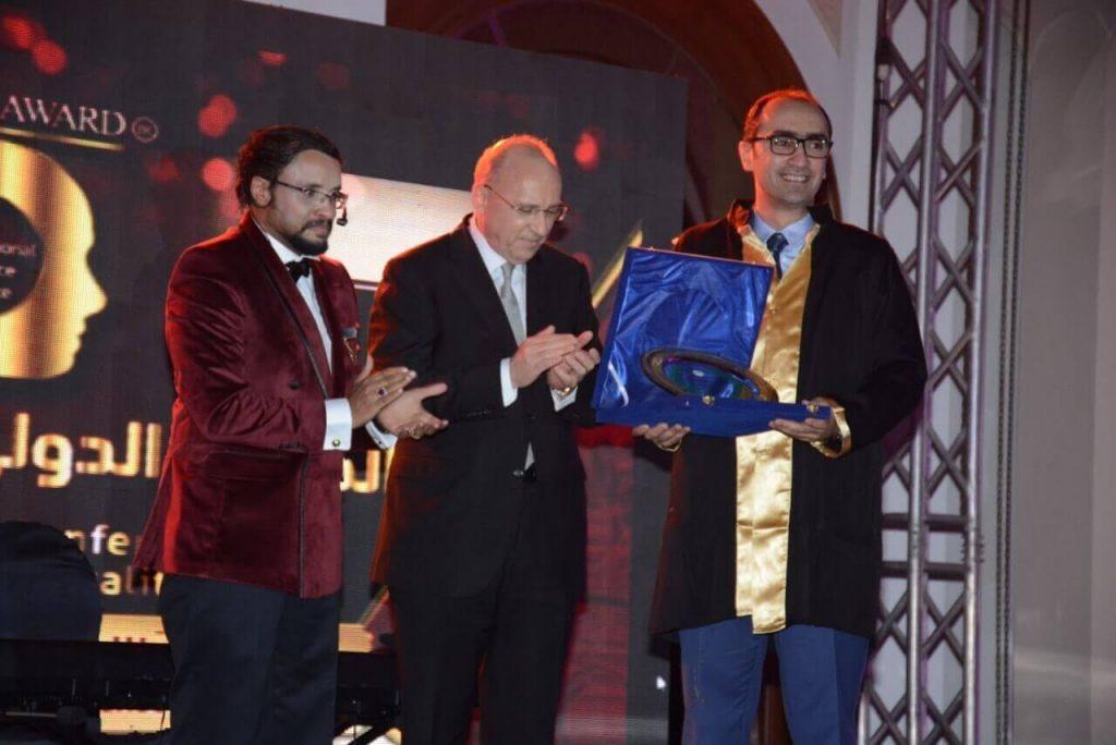 dr mustafa showing off his award
